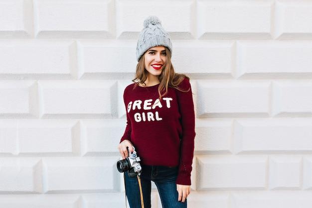 Młoda dziewczyna z długimi włosami w sweter marsala na szarej ścianie. nosi dzianinową czapkę, trzyma aparat i uśmiecha się.