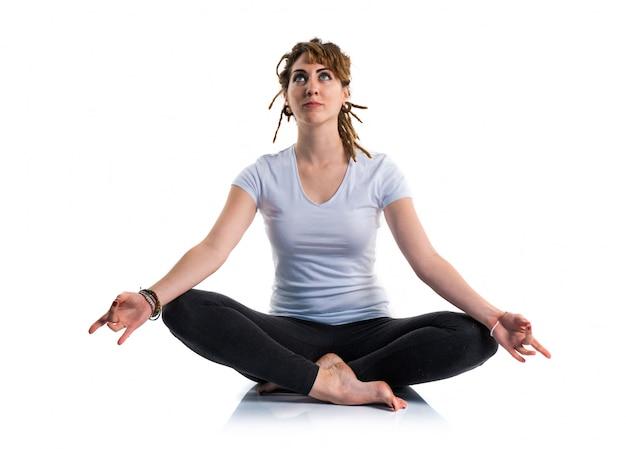 Młoda dziewczyna z dreadlocks robi joga