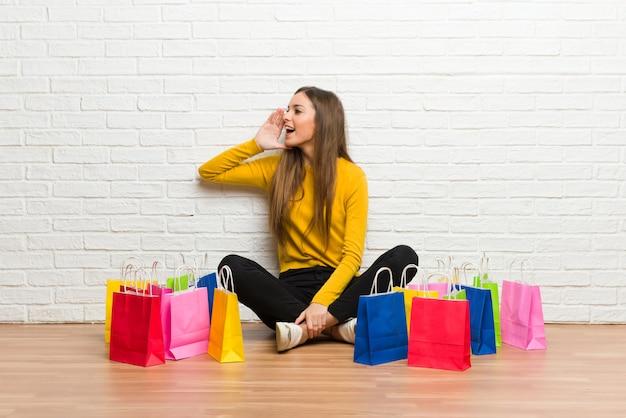 Młoda dziewczyna z dużą ilością torby na zakupy krzyczy z szeroko otwartymi ustami do boku