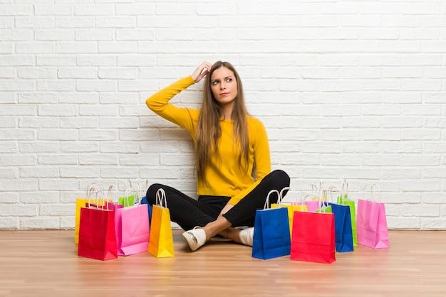 Młoda dziewczyna z dużą ilością torby na zakupy o wątpliwości podczas drapania głowy