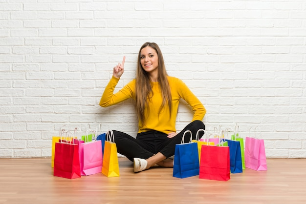 Młoda dziewczyna z dużą ilością torby na zakupy pokazując i podnosząc palec na znak najlepszych