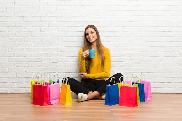 Młoda dziewczyna z dużą ilością torby na zakupy trzyma filiżankę gorącej kawy