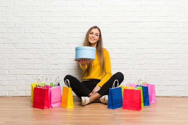 Młoda dziewczyna z dużą ilością torby na zakupy trzyma prezent w rękach