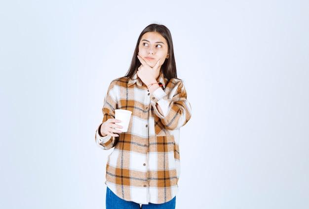 Młoda dziewczyna z filiżanką herbaty myślenia na białej ścianie.