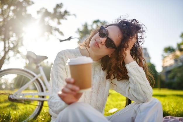 Młoda dziewczyna z filiżanką kawy wygląda na zrealizowaną