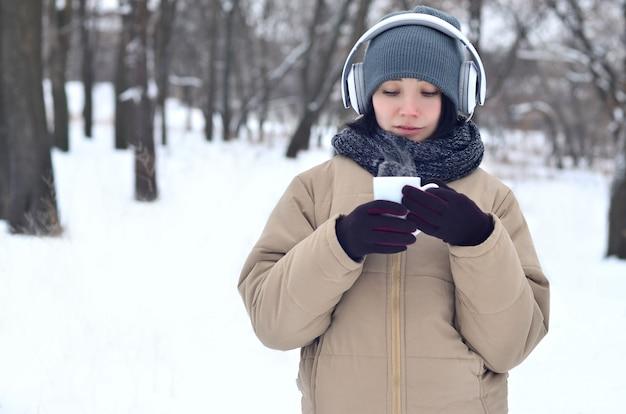 Młoda dziewczyna z hełmofonami i filiżanką