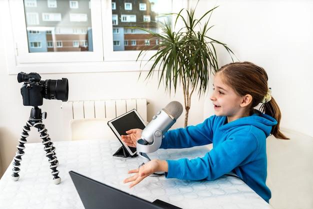 Młoda dziewczyna z influencerką i blogerka transmituje na żywo ze swojego salonu, śmiejąc się i świetnie się bawiąc, patrząc w kamerę i mówiąc do mikrofonu na platformie wideo lub w sieci społecznościowej