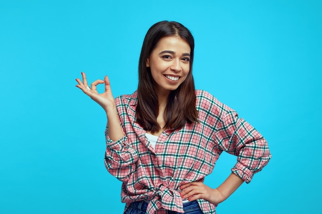 Młoda dziewczyna z jasnym uśmiechem na sobie zwykłą koszulę i pokazuje gest ok na niebieskiej ścianie