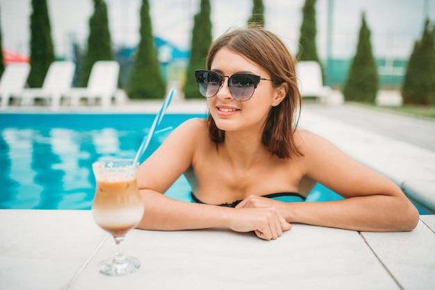 Młoda dziewczyna z koktajlem w pobliżu basenu. szczęśliwa kobieta zrelaksować się na wakacjach. podróże w ośrodku