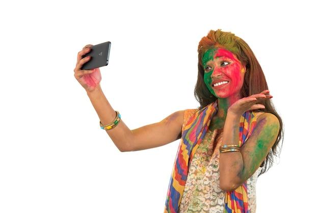 Młoda dziewczyna z kolorową twarzą, biorąc selfie za pomocą smartfona na festiwalu holi. festiwal i koncepcja technologii na białym tle.