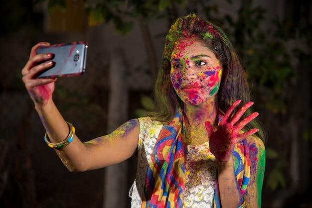 Młoda dziewczyna z kolorową twarzą, biorąc selfie za pomocą smartfona na festiwalu holi. koncepcja festiwalu i technologii.