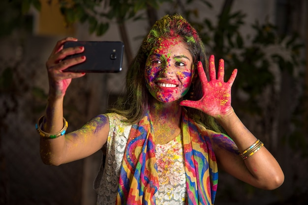 Młoda dziewczyna z kolorową twarzą przy selfie za pomocą smartfona na festiwalu holi