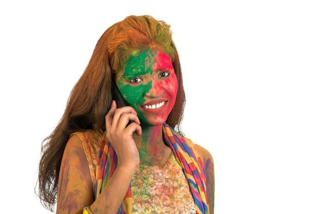 Młoda dziewczyna z kolorową twarzą rozmawia przez telefon i świętuje festiwal kolorów holi.
