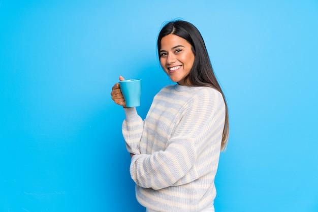 Młoda dziewczyna z kolumbii w swetrze, trzymając filiżankę gorącej kawy