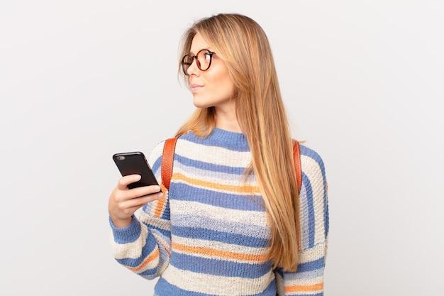 Młoda dziewczyna z komórką na widoku profilu myśląca, wyobrażająca sobie lub marząca