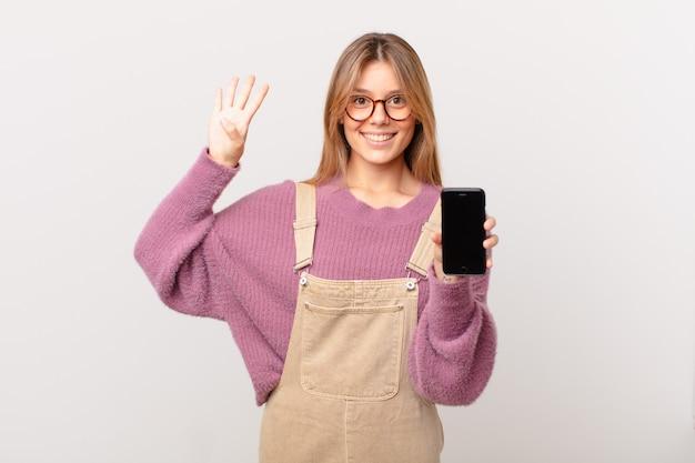 Młoda dziewczyna z komórką uśmiechnięta i wyglądająca przyjaźnie, pokazująca numer cztery