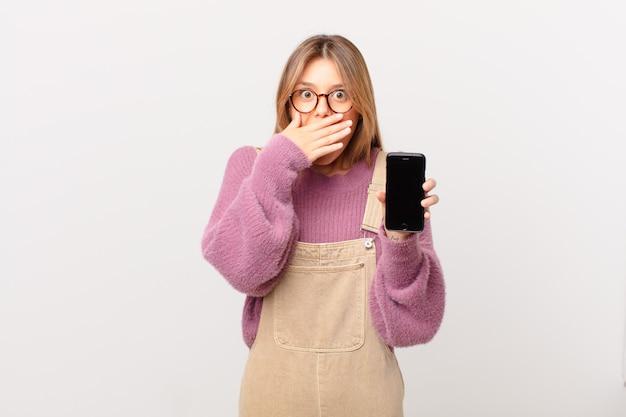 Młoda dziewczyna z komórką zakrywającą usta dłońmi w szoku