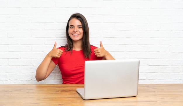 Młoda dziewczyna z komputerem osobistym w stole daje aprobata gestowi
