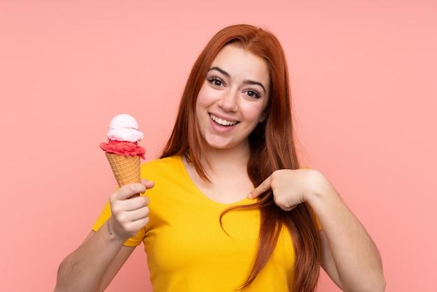 Młoda dziewczyna z kornetem lody nad odosobnioną ścianą z niespodzianka wyrazem twarzy