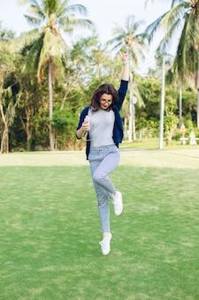 Młoda dziewczyna z krótkimi ciemnymi włosami, skoki w parku z palmami
