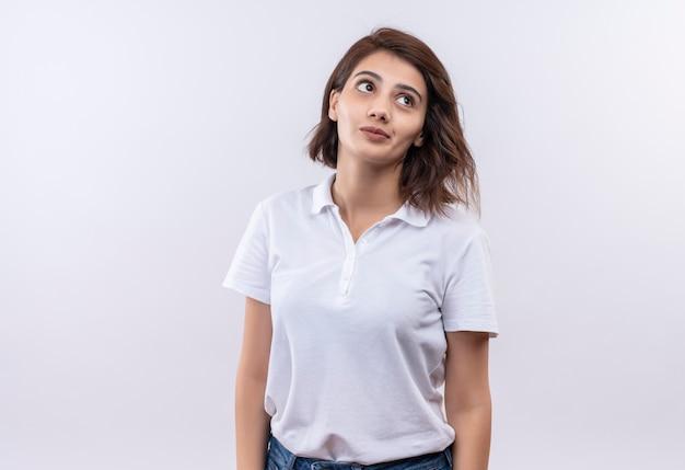 Młoda dziewczyna z krótkimi włosami na sobie białą koszulkę polo patrząc na bok ze smutnym wyrazem twarzy
