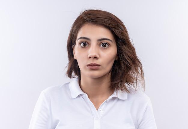 Młoda dziewczyna z krótkimi włosami na sobie białą koszulkę polo patrząc na kamery zaskoczona i zdumiona