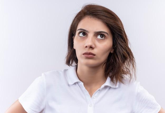 Młoda dziewczyna z krótkimi włosami na sobie białą koszulkę polo patrząc z podejrzanym wyrazem twarzy