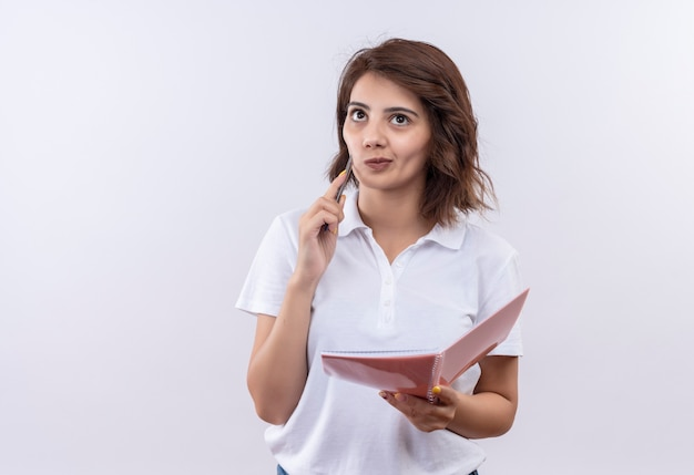 Młoda dziewczyna z krótkimi włosami na sobie białą koszulkę polo trzymając notatnik i długopis patrząc na bok z zamyślonym wyrazem, myśląc