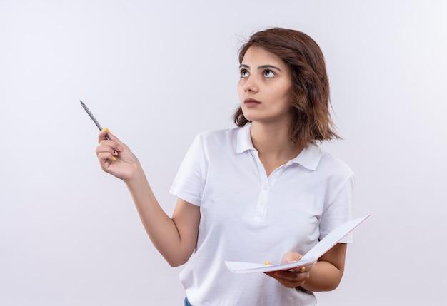 Młoda dziewczyna z krótkimi włosami na sobie białą koszulkę polo, trzymając notatnik i długopis patrząc na bok z zamyślonym wyrazem twarzy