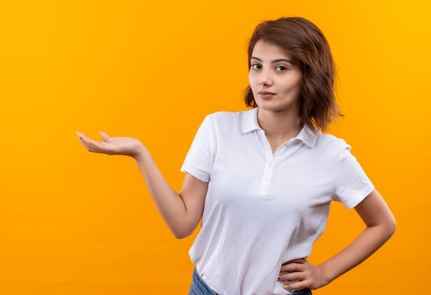 Młoda dziewczyna z krótkimi włosami na sobie koszulkę polo uśmiechnięty pewny siebie, przedstawiając ręką