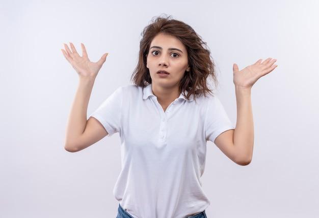 Młoda dziewczyna z krótkimi włosami, ubrana w białą koszulkę polo, wyglądająca na niepewną i zdezorientowaną, wzruszającą ramionami, nie mając odpowiedzi