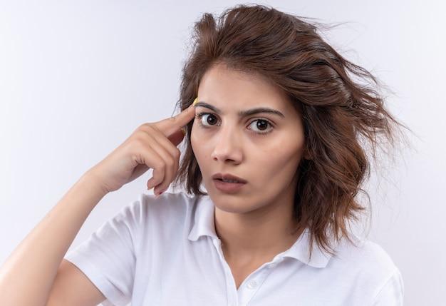 Młoda dziewczyna z krótkimi włosami ubrana w białą koszulkę polo wyglądająca na zdezorientowaną i zmartwioną wskazującą na jej skroń