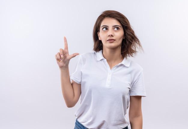 Młoda dziewczyna z krótkimi włosami, ubrana w białą koszulkę polo, zaintrygowana, wskazująca palcem wskazującym w górę