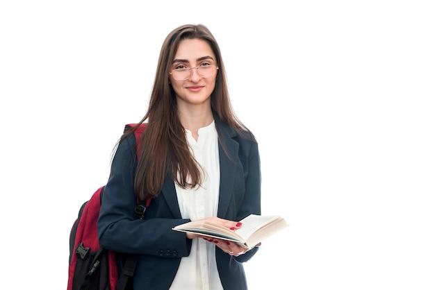 Młoda dziewczyna z książkami i torbą na białym tle