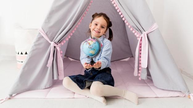 Młoda dziewczyna z kulą ziemską pozuje w namiocie