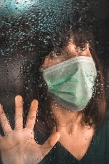 Młoda dziewczyna z maską w pandemii covid-19, wyglądająca przez okno w deszczowy dzień