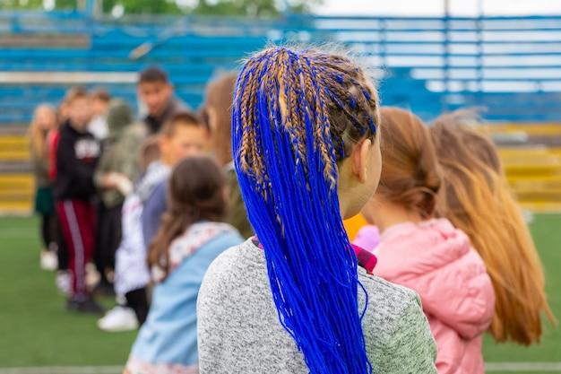 Młoda dziewczyna z modną fryzurą z plecionymi niebieskimi wstążkami we włosach, niebieskie włosy. niezwykła fryzura