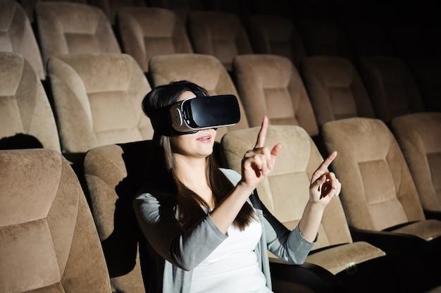 Młoda dziewczyna z okularami wirtualnej rzeczywistości w miękkim fotelu.