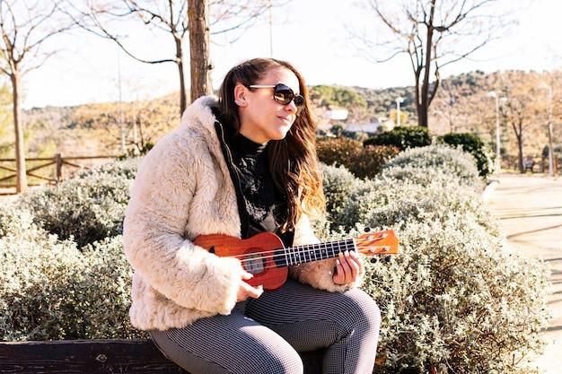 Młoda dziewczyna z okulary gra na ukulele w parku