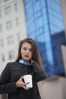 Młoda dziewczyna z papierowym kubkiem kawy na świeżym powietrzu