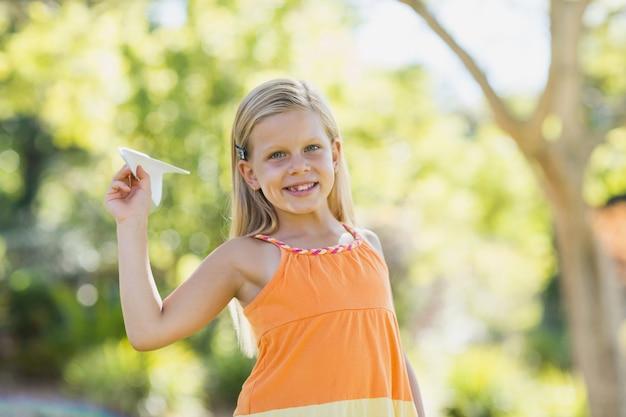 Młoda dziewczyna z papierowym samolotem w parku