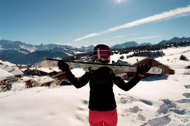 Młoda dziewczyna z parą nart i kasku narciarskiego patrząc na horyzont w ośrodku narciarskim w alpach