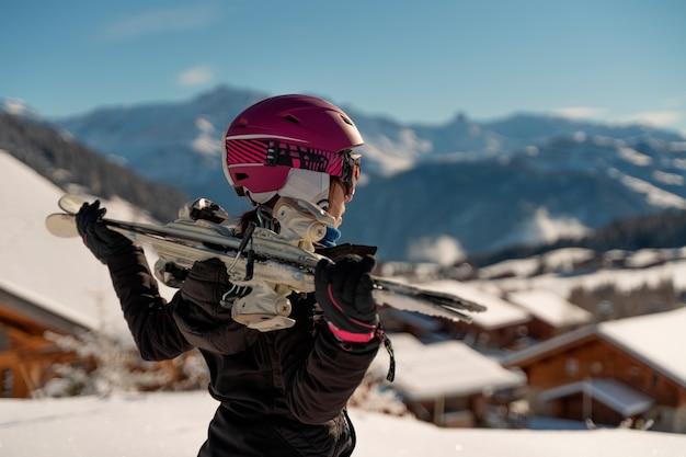 Młoda dziewczyna z parą nart i walizką na nartach, patrząc na horyzont w ośrodku narciarskim w alpach