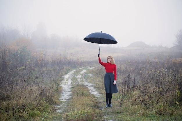 Młoda dziewczyna z parasolem w jesieni polu