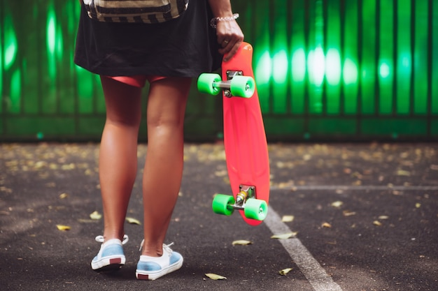 Młoda dziewczyna z plastikowym pomarańczowym shortboard grosza za zieloną ścianą w czapce