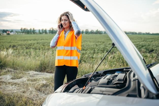 Młoda dziewczyna z połączeń telefonicznych do pogotowia, zepsuty samochód. kłopoty z pojazdem na drodze w letni dzień. kobieta w odblaskowej kamizelce