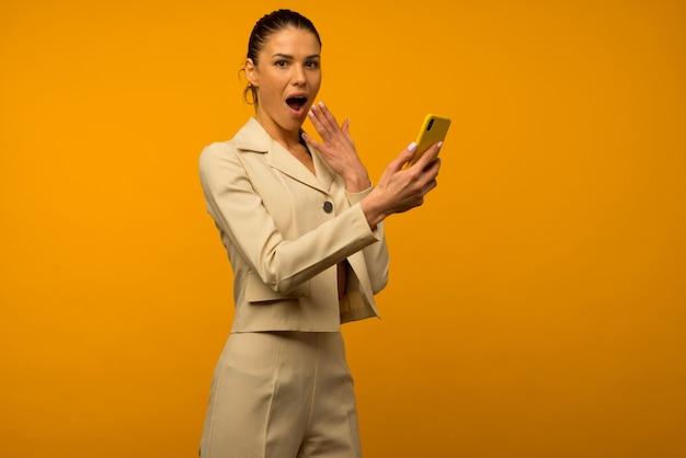Młoda dziewczyna z problemami skóry twarzy pozuje ze smartfonem na żółtym tle.