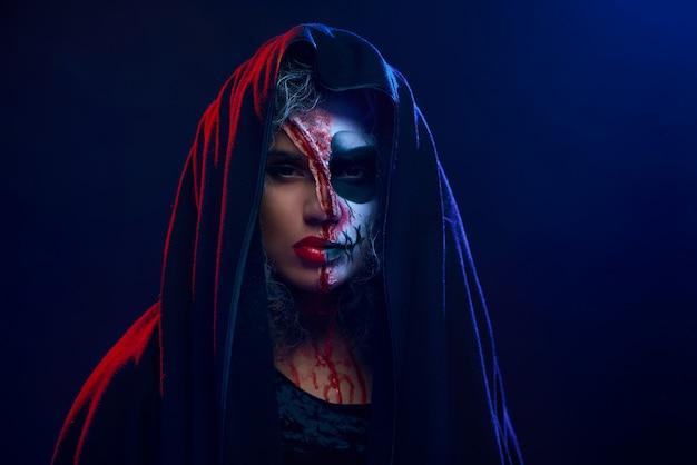 Młoda dziewczyna z przerażającym makijażem i płaszczem zakryła głowę