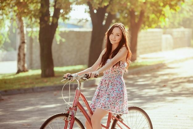 Młoda dziewczyna z rowerem w parku