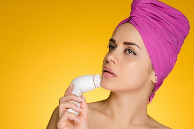 Młoda dziewczyna z różowym ręcznikiem na głowie dokonuje głębokiego oczyszczania twarzy za pomocą elektrycznej szczoteczki